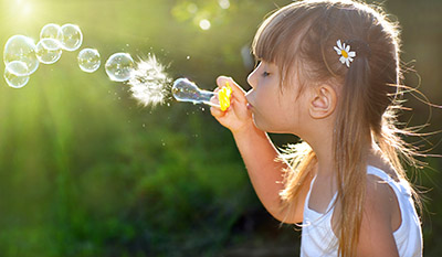 Girl Blowing Bubbles - Pediatric Dentist and Orthodontist in Houston, Pearland and Pasadena, TX